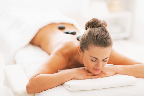 Massage therapy in Calgary | Young woman receiving hot stone massage